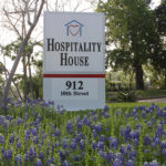 Hospitality House - 912 10th Street sign in front of house with bluebonnets around it